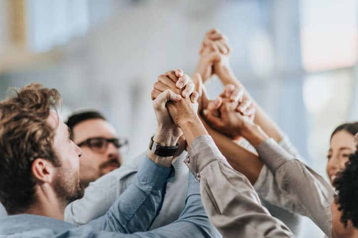 Coworkers holding each other's hands raised in the air to show resilience