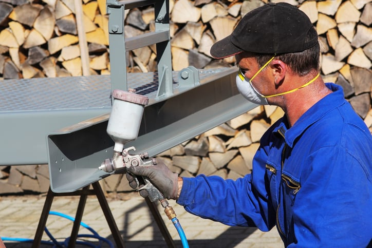 Worker in mask spraying steel with ISO 12944 corrosion protection paint.