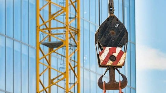 Red and white below-the-hook lifting device in construction site designed to ASME BTH-1-2020.