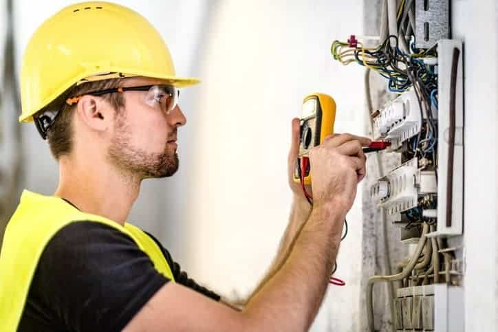 Man in yellow hardhat testing wiring system with the National Electrical Code (NEC), or NFPA 70-2017
