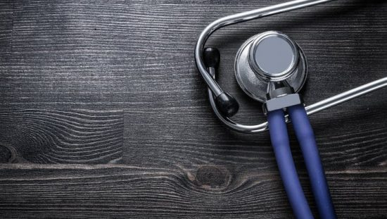 Stethoscope on wood adhering to ISO 15223-1:2016 for symbols on medical device labels