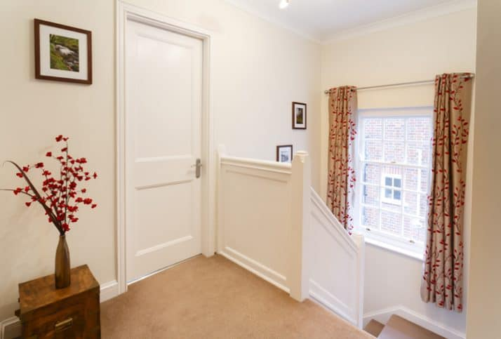 Upstairs landing in a house, next to a closed bedroom door