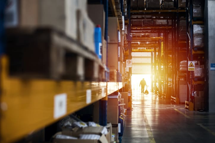 Man walking from warehouse interior at sunset after following ANSI/ITSDF B56.1-2020 for forklifts and trucks