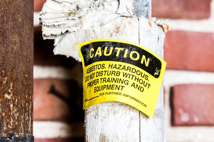Yellow asbestos warning on broken pipe than cannot be ignored when properly removing and disposing during construction.