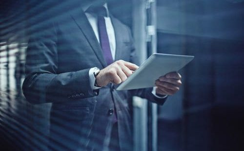 Businessman on tablet with some great Six Sigma competencies (under ISO standards).