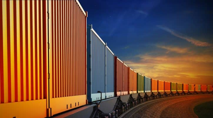 Railroad lineup of colorful ASTM D4169-16 performance-tested shipping containers under sunset.