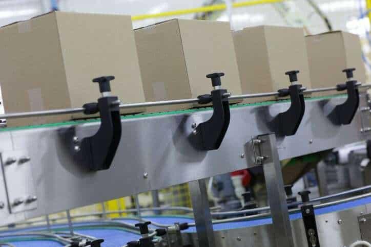 Boxes sliding down conveyor adhering to ANSI/PMMI B155.1-2016.