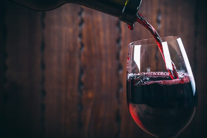 Pouring some good red wine, which has been made to ISO wine making standards.
