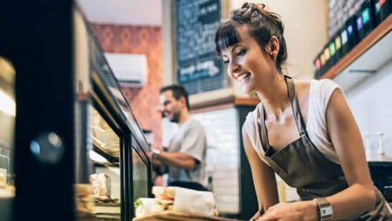Woman working at a deli, making quality sandwiches and knowing what to do thanks to ISO 9001:2015 for Small Enterprises.