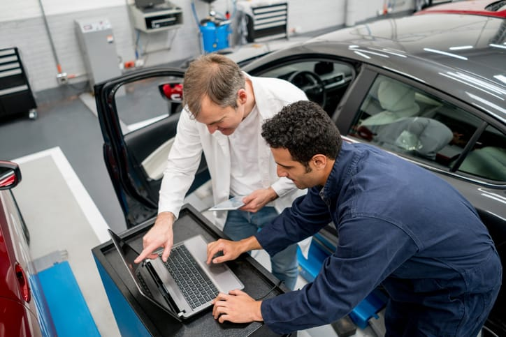Two workers in garage depending on the AIAG CQI-20:2018 Problem Solving Guideline.