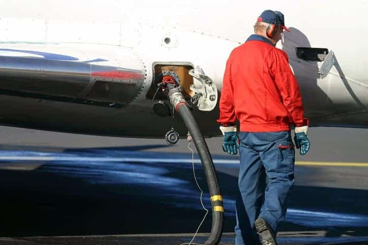 Man in old red windbreaker pumping jet fuel in plane to ASTM D1566-20 specifications.