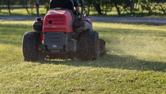 Riding a ANSI/OPEI B71.4 lawnmower to take care of the turf, or grass.