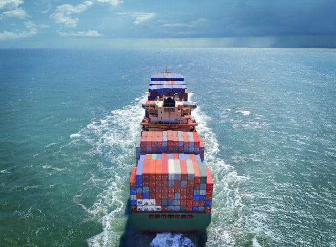 Barge in open sea loaded with ASTM D4169-16 shipping containers.