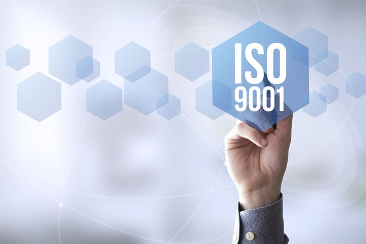 Hand reaching to ISO 9001:2015 graphic for quality management system requirements and certification / accreditation.