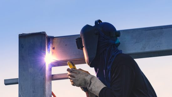 Worker joining metals in building weld while following AWS A2.4:2020 for standard welding symbols.