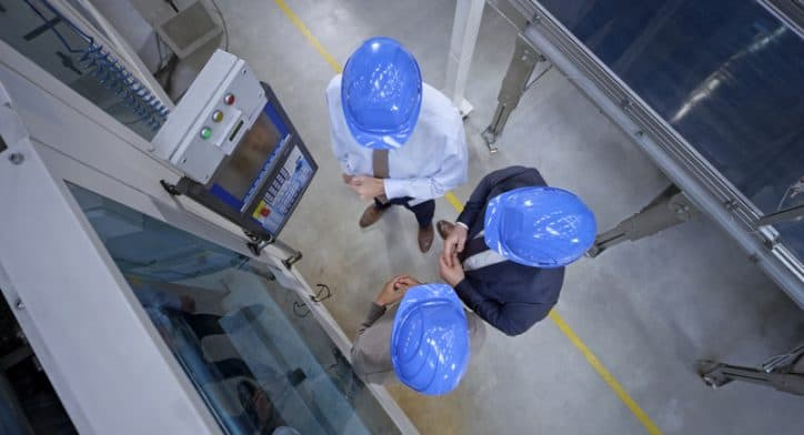 Three managers in blue hardhats abiding to ANSI B11 standards while looking at a safe machine in factory.