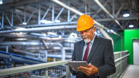 Old man executive taking an active role in warehouse's quality management practices as an ISO 9001:2015 leader.