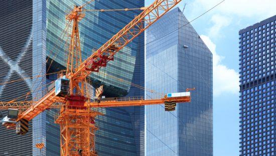 Bright red tower crane in operation in Dubai.