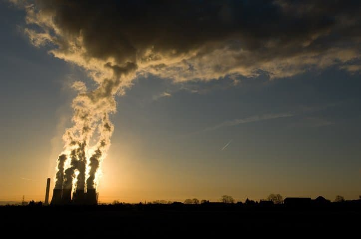 Power plant emits smoke and in need of ISO 14064 standards for quantifying greenhouse gas emissions.