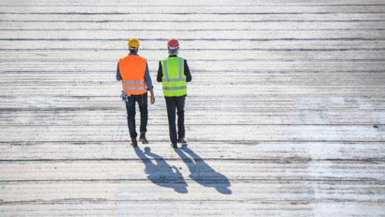 Two construction guys walking on boardwalk from behind and donning ANSI/ISEA 107-2020 high visibility apparel.