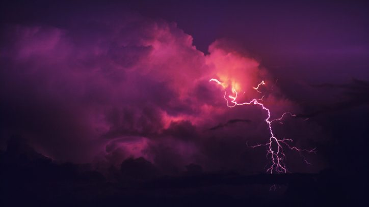 Red thunderstorm crashing in the clouds to represent overvoltages from not rating to ANSI C84.1-2020.