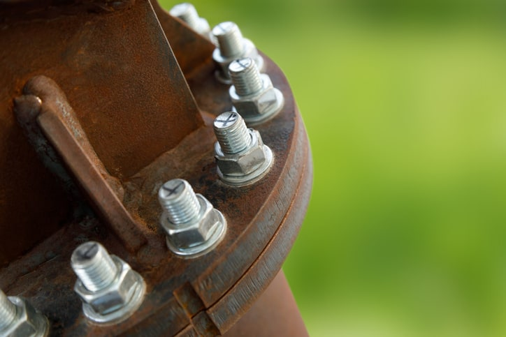 Chrome screws poking out of rusty petroleum piping system with ASME A13.1-2020 marking.