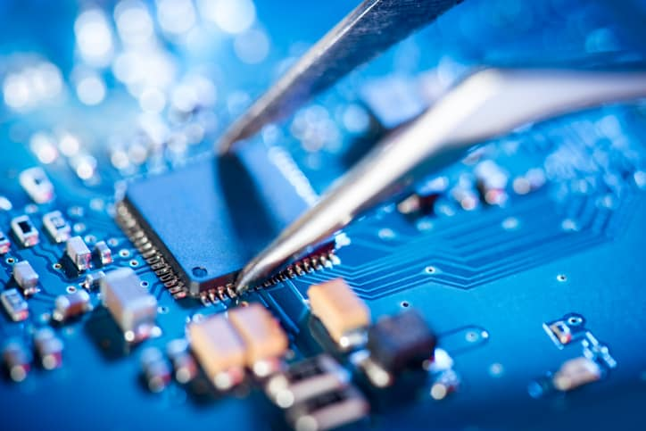 Blue circuit board being checked via IPC A-610H-2020 acceptability of electronic assemblies defect and problem testing.