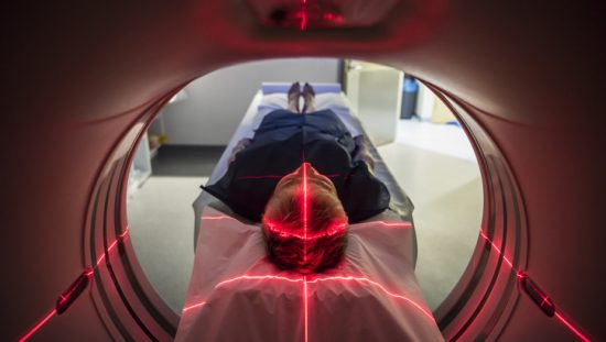 Patient undergoes red light of PET scan and CAT scan technology refurbished to IEC 63077 medical imaging requirements.