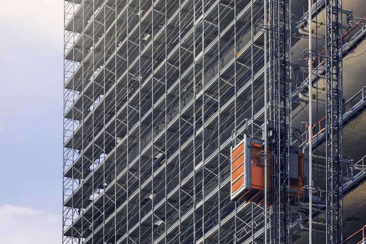 Hoist elevators that follow ANSI/ASSE A10.4-2016 on the side of a building in the process of being constructed.