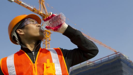 Construction worker in bright yellow HVSA drinking from a water bottle to combat the summer heat.