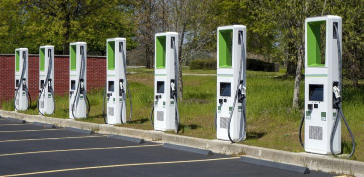 Green electric vehicle charging stations lined up in mall parking lot in IEC 61851 adherence.