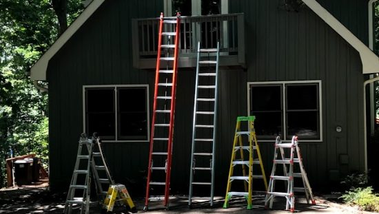 Ladders leaning against a cabin in the woods during National Ladder Safety Month