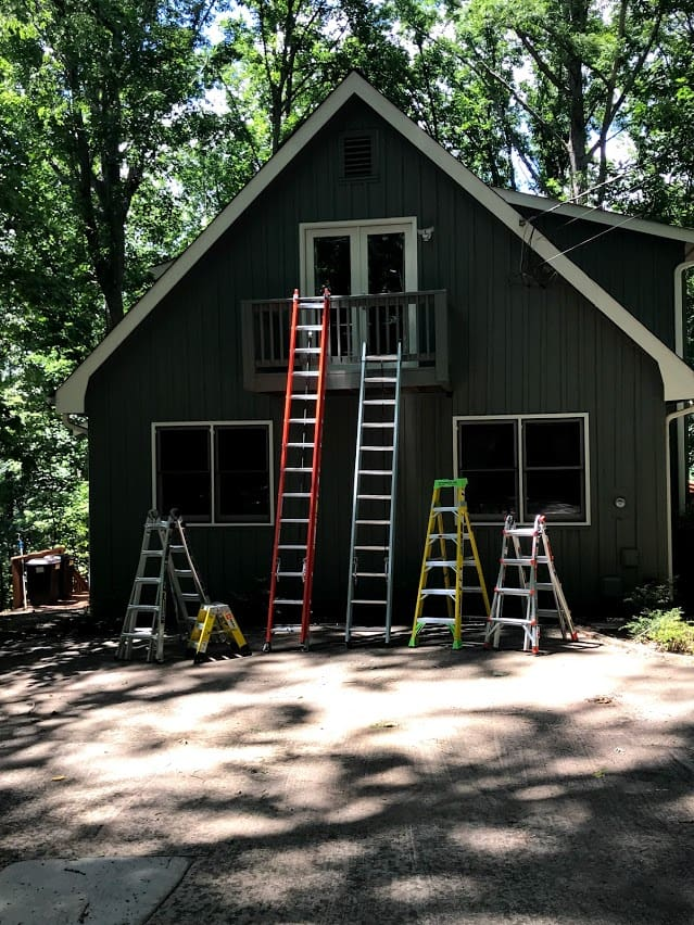 Half dozen colorful ladders safely leaning against small home.
