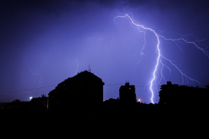 Lightning striking house in blue darkness, prompting need for IEEE C62.41.3-2020 surge protective devices.