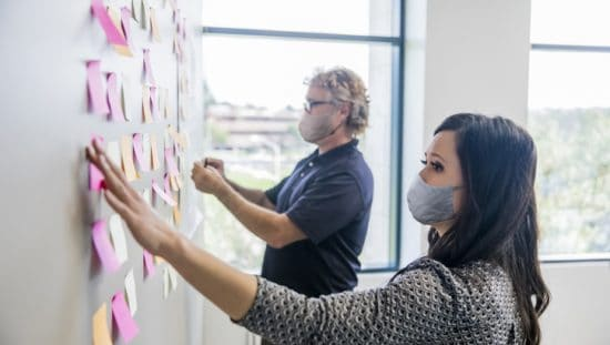 Two project managers wearing face masks and organizing tasks in accordance with ISO 21502:2020 guidance.