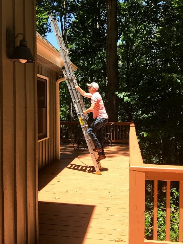 Man climbing ladder at cabin porch using three points of contact.