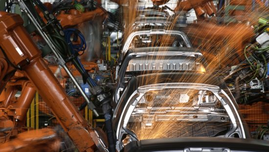Robot arms manufacturing automobiles in compliance with IATF 16949 and ANAB accredited laboratories.