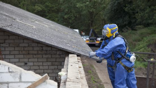 Workers in blue PPE removing asbestos on a dilapidated roof during abatement process.