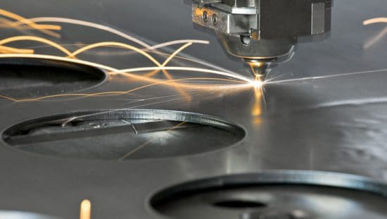 CNC machining slicing through metal with a laser with standard tooling parts.