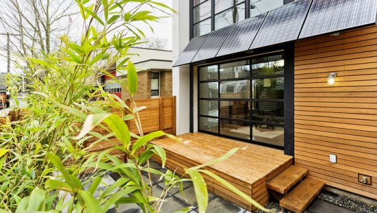 Wood home with greenery adhering to best International Energy Conservation Code (IECC) requirements.