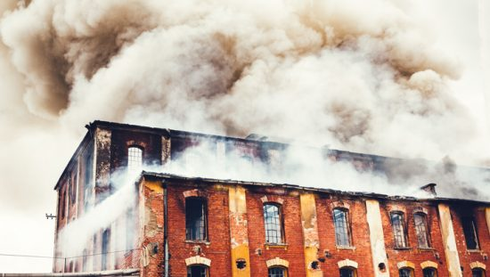 Smoke rising above old brick factory fire that didn't follow the 2021 International Fire Code (ICC IFC-2021).
