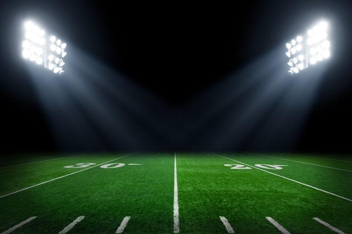 Verdant football field at night with stadium lights set properly with ANSI/IES RP-5-21 illumination.