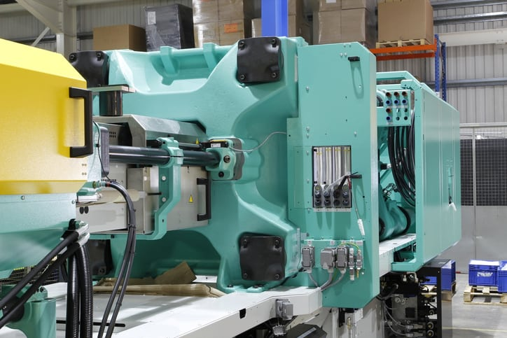 A green injection molding machine using robots kept safe by ANSI/PLASTICS B151.27-2021 safety requirements.