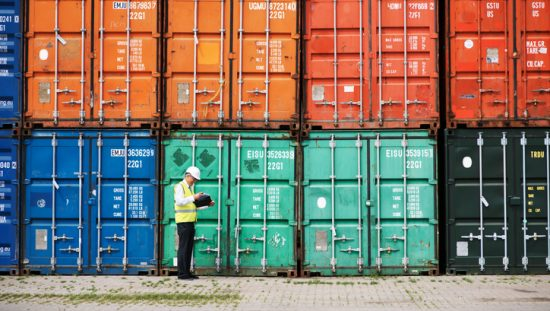 Manager walking beside colorful shipping containers and checking on supply chain security through SCS 9001.