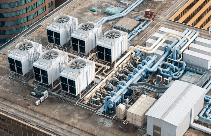 White mechanical building systems with spinning fans on HVAC systems safely following the 2021 International Mechanical Code (IMC).