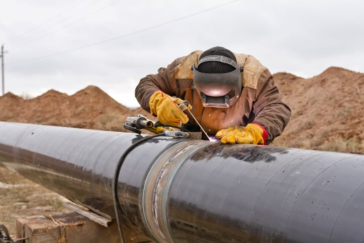 Worker covered in PPE in the plains welding a black pipeline with proper ASME B31Q-2021 pipeline personnel qualifications.