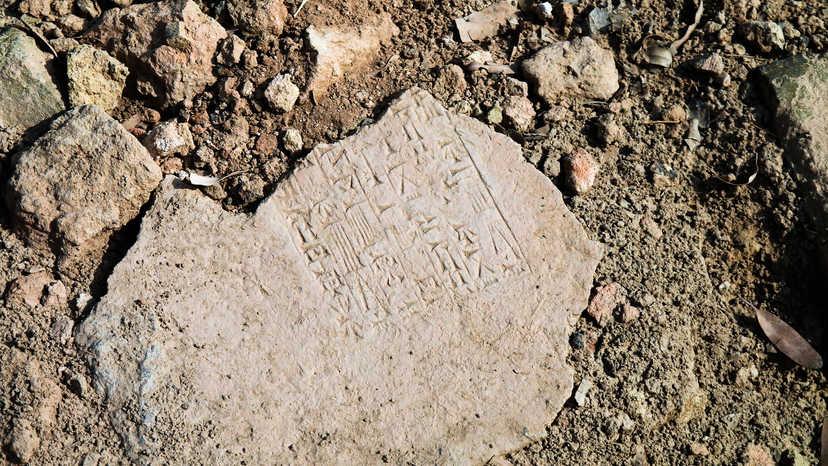Broken cuneiform tablet in the dirt written in ancient language Akkadian, or in a ISO 639-2 code, akk.