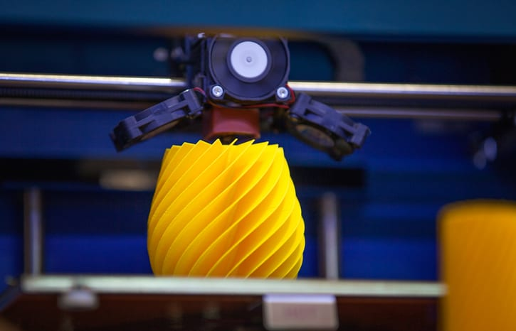 A yellow spiral object being 3D printed according to ISO/ASTM 52900 terminology.
