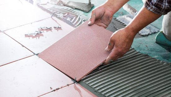 Man installs ceramic tile on floor while following ANSI TCNA guidelines.