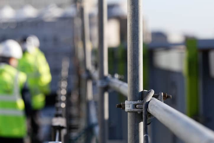 Steel scaffolding of construction site at height that workers need ANSI/ASSP Z359.14-2021 self-retracting devices.